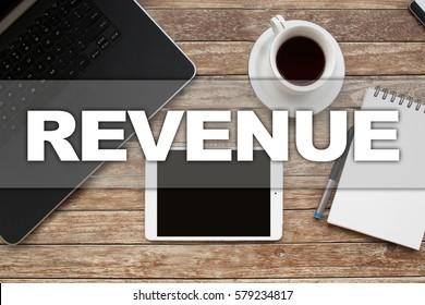 Tablet on desktop with revenue text.