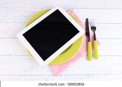 Tablet on plate with fork and knife on wooden background