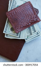 tablet on the table in a leather pouch and a leather purse with money