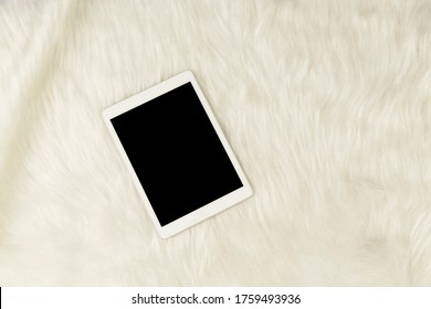 tablet on woolly fur on white background