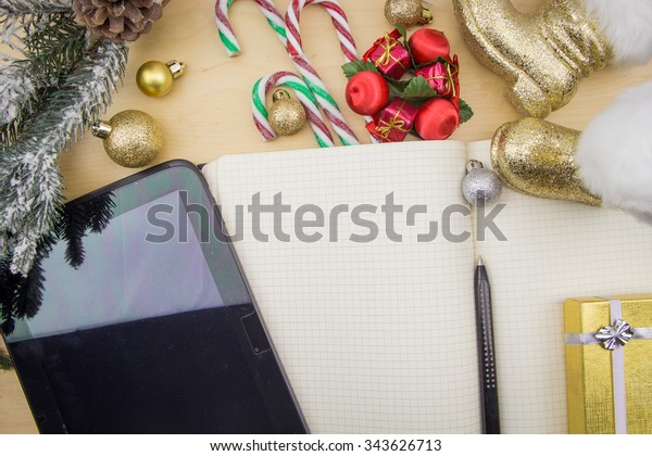 Tablet and open notebook with winter festive ornaments.