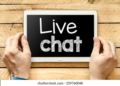 Tablet pc with live chat. Male hands holding tablet pc with live chat on wooden background