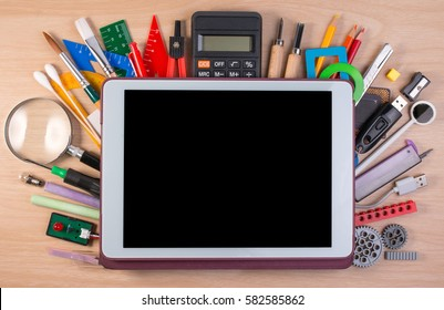 Tablet PC over school supplies or office supplies on school table. Background with school or office material with copy space for text.