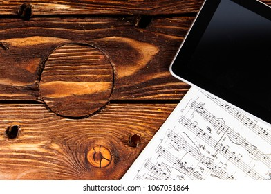 Tablet PC and sheet music on the table. Composing music.