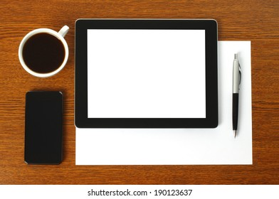 Tablet PC, smart phone, paper, pen and cup of coffee on wooden background