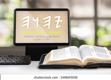 A tablet showing the paleo Hebrew symbols for the name of God on a desk with a keyboard, opened holy bible and cross in background.