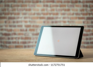 Tablet standing on a wooden table in front of a brick wall. copy space.