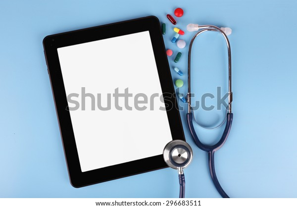 Tablet with stethoscope and tablets on blue background