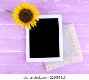 Tablet and sunflower on napkin on wooden background