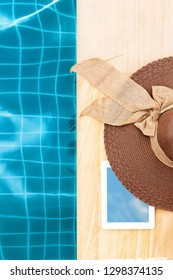 Tablet and sunhat near blue swimming pool from above. Working on holidays concept.