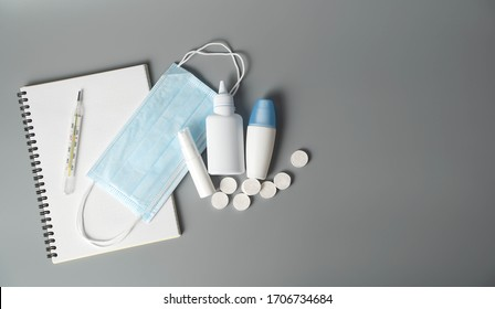Tablet, thermometer and protective equipment: alcohol gel, napkins, masks on a gray background. The concept of protecting and disinfecting the workspace from viruses and bacteria.