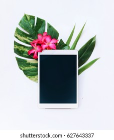 Tablet with tropical flowers on a white background