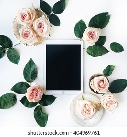 Tablet, vintage golden tray, retro plate and pink rose flower with green leaves on white background. Top view, flat lay