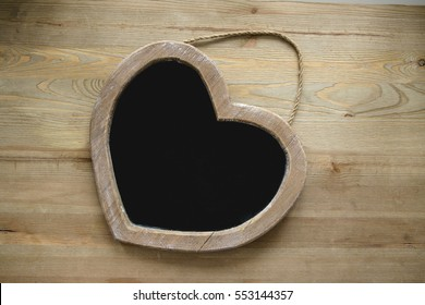 The tablet of wood for writing with chalk, in the shape of a heart on a wooden background