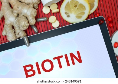 Tablet with words Biotin, pills, lemon and ginger. Healthy eating.