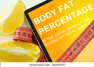 Tablet with words body fat percentage and measuring tape