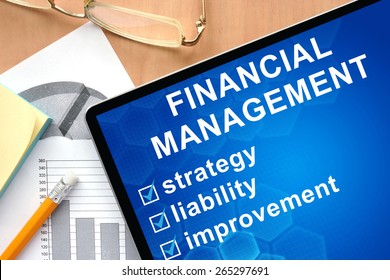 Tablet with words financial management. Business and management concept.