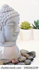 Tabletop Buddah mit polierten Steinen und sukkulenten Pflanzen in vertikaler Zusammensetzung in sanftem Fenster.  Ruhige und kontemplative Stimmung.