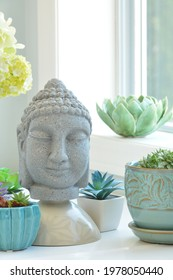 Tabletop Buddah surrounded by succulent plants and ceramic lotus in vertical composition in soft window light.  Peaceful and contemplative mood.