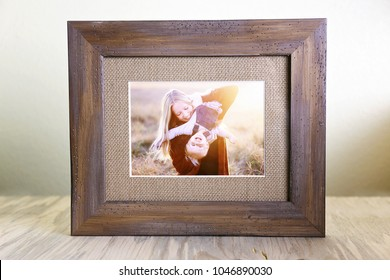 A tabletop display of a rustic wood framed print holding a portrait of a happy young mother holding her baby daughter outside at suset.