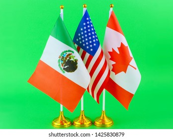 Tabletop flags of the United States, Canada and Mexico, who all share a political relationship and a partnership called the United States–Mexico–Canada Agreement. The flags are on a green screen.