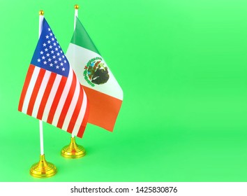 Tabletop flags of the United States and Mexico, who share a border and have a political relationship. The flags are together and on a green screen to allow for any background.