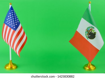 tabletop flags of the United States and Mexico, who share a border and have a political relationship. The flags are on either side of the image and are on a green screen to allow for any background.