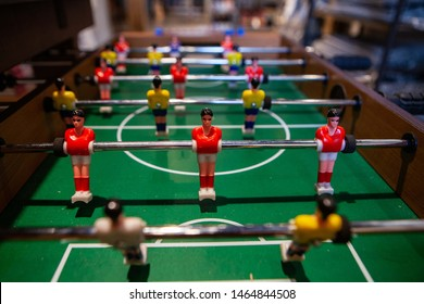 Tabletop football game in bachelor pad. A closeup view of a table football game, typically found in student accommodation, also called foosball, small plastic figures controlled on rods.