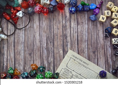 Tabletop role playing flat lay background with colorful RPG dices and character sheet on wooden desk