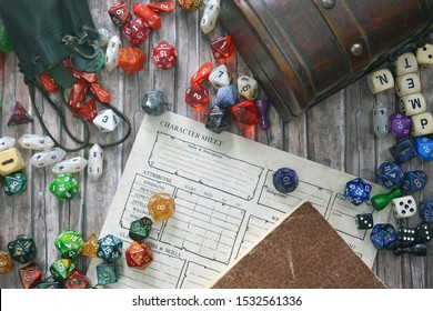 Tabletop role playing flat lay with colorful RPG and game dices,  character sheet, rule book and treasure chest on wooden desk