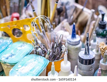 A tabletop of tools hold items a potter will use, including containers of glazes, brushes and carving tools