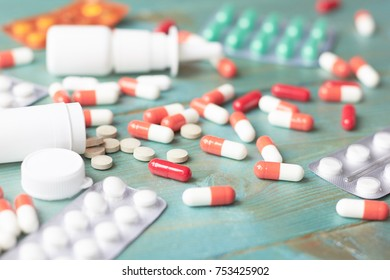 Tablets and capsules are scattered on the table