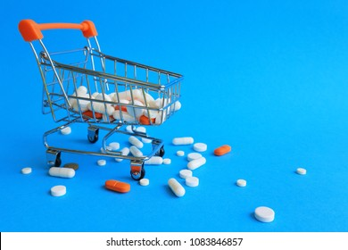 Tablets, capsules and a shopping cart on a blue background. The concept of buying drugs, prices for treatment. Sales in the pharmacy.