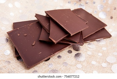 Tablets to pieces of fine dark chocolate in studio.