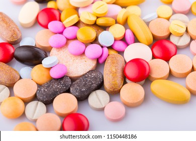 Tablets pills capsule heap mix therapy drugs, over a white background
