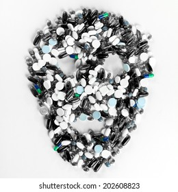 Tablets, pills and capsules, that shape a creepy skull on white background