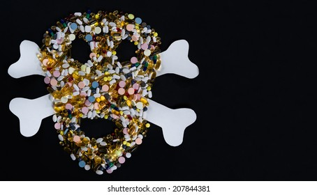 Tablets, pills and capsules, that shape a creepy skull on black background with copy space.