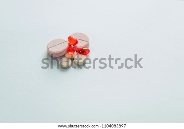 TABLETS OF RED AND PINK COLOUR ON THE WHITE BACKGROUND