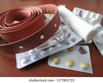 Tablets, a tourniquet and a bandage lying on a brown table. Brown tourniquet to stop the bleeding.
