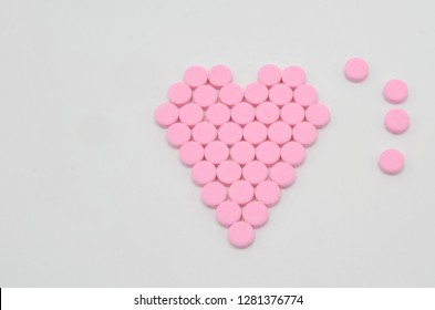 Tablets of warfarin sodium in the shape of a heart against a white background. Warfarin is a Vitamin K antagonist which is used for preventing the blood from clotting.