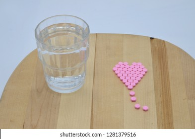 Tablets of warfarin sodium in the shape of a heart against a wooden background with a glass of water. Warfarin is a Vitamin K antagonist which is used for preventing the blood from clotting.
