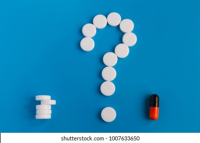 The tablets are white meds on a blue background. A symbol of a question mark. Choose between multiple pills and medical pills. Conceptual for pharmaceutical