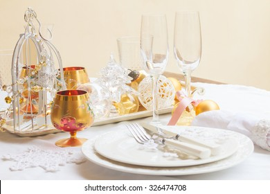Tableware for christmas - plates, cups and utensils  with white table cloth and christmas golden decorations