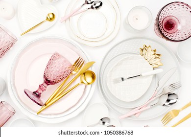 Tableware and decorations for serving a festive table.  Plates, wine glasses and cutlery with  decorative textile on white background.