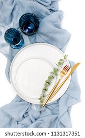 Tableware and decorations for serving a festive table.  Plates, wine glasses and cutlery with gray decorative textile on white background.