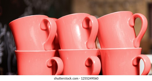 tableware and design concept - six stacked cups in trendy color of the year 2019 living coral