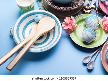 Tableware dish set on blue pastel background with flowers. Flat lay