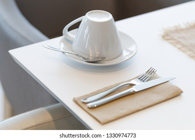 tableware in the elegant interior of a restaurant - cups, cutlery on the white table and bright blurry background