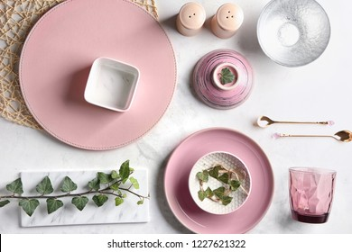 Tableware and floral decor on light background