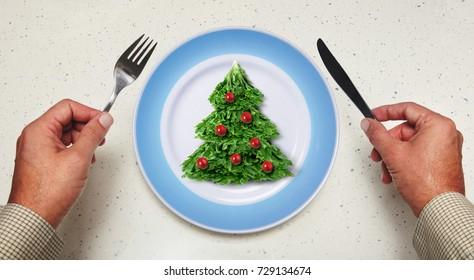 tableware in hands and holiday salad on a plate
